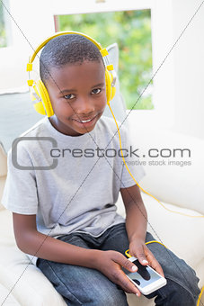 Little boy listening to music on the couch