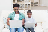 Father and son using laptops on the couch