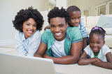 Happy family lying on the floor using laptop