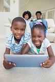 Happy siblings lying on the floor using tablet