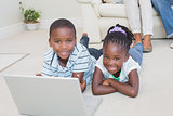 Happy siblings lying on the floor using laptop