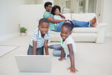 Happy siblings sitting on the floor using laptop