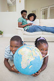 Happy siblings lying on the floor holding globe
