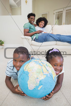 Happy siblings lying on the floor holding globe