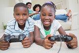 Happy siblings lying on the floor playing video games