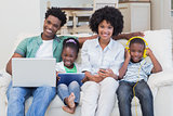 Happy family using technologies on the couch