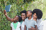 Happy family taking selfie with tablet pc