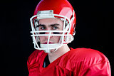 Portrait of a serious american football player taking his helmet looking at camera