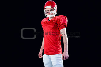A serious american football player taking his helmet looking at camera
