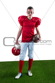 A serious american football player taking his helmet on her hand looking at camera