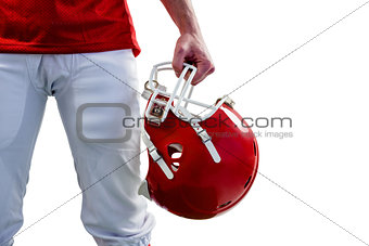 An american football player taking his helmet on hand