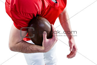 American football player taking a ball on her hand