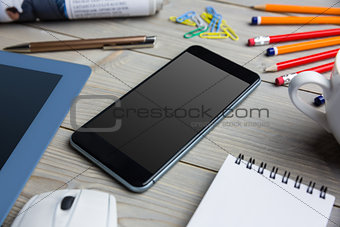 Smartphone next to the cup notepad tablet