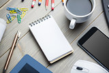 Notepad next to the cup of coffee smartphone mouse and tablet