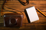 Notepad next to camera and pen