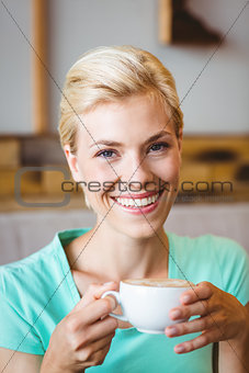 Pretty blonde looking at camera and holding cup of coffee