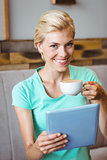 Pretty blonde holding cup of coffee and using tablet computer