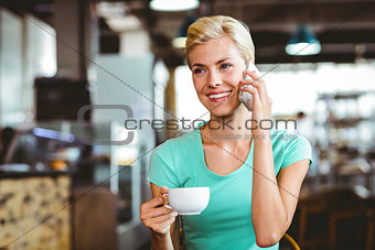 Pretty blonde woman using her smartphone with a cup of coffee