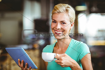Pretty blonde having a coffee using tablet pc