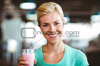 Smiling blonde woman enjoying her milkshake