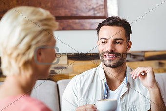Couple with coffee cup sitting on sofa
