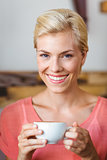 Pretty blonde woman smiling at camera and holding a cup of coffee