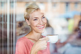 Happy blonde woman drinking a cup of coffee