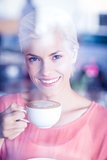 Happy blonde woman smiling at camera and holding a cup of coffee