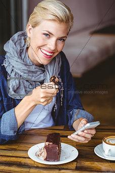 Smiling blonde enjoying a piece of chocolate cake