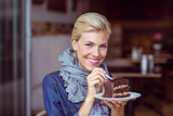 Smiling blonde taking a piece of chocolate cake