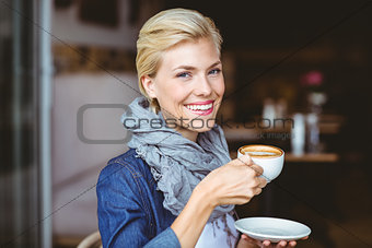 Smiling blonde enjoying a cup of cappuccino