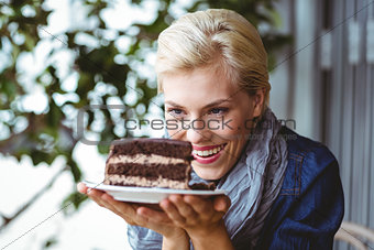 Smiling blonde looking a chocolate cake