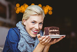 Smiling blonde holding a chocolate cake