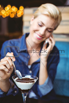 Smiling blonde eating a creamy chocolate