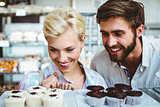 Cute couple on a date looking at cakes