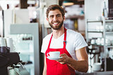 Handsome barista holding a cup of coffee