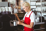 Pretty barista using the coffee machine