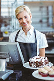 Smiling employee using calculator on counter
