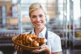 Cheerful gorgeous waitress holding a basket with croissant