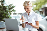 Young woman having a piece of pie using laptop