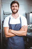 Smiling server in apron arm crossed