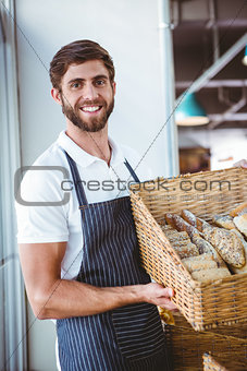 Portrait of happy worker holding basket of bread