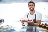 Smiling worker holding cupcakes behind the counter
