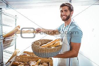 Portrait of happy worker holding basket of bread