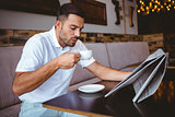 Young man drinking cup of coffee reading newspaper
