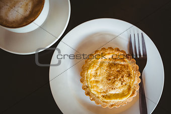 Close up view of a pastry beside a cappuccino