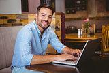 Smiling businessman using his laptop