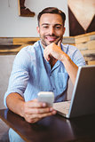 Smiling businessman using his laptop