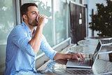 Young businessman drinking coffee beside a laptop