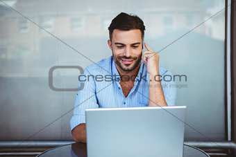 Smiling businessman on the phone working on laptop